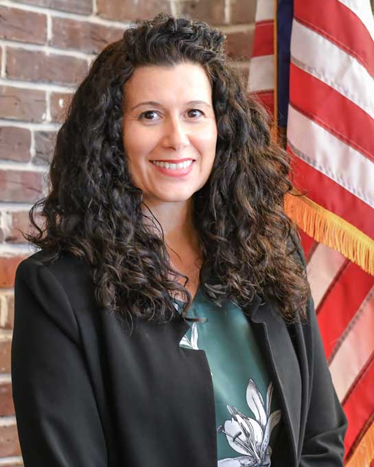 Nikki-Approved-Headshot_black-jacket_green-top_historic-courthouse-with-flag