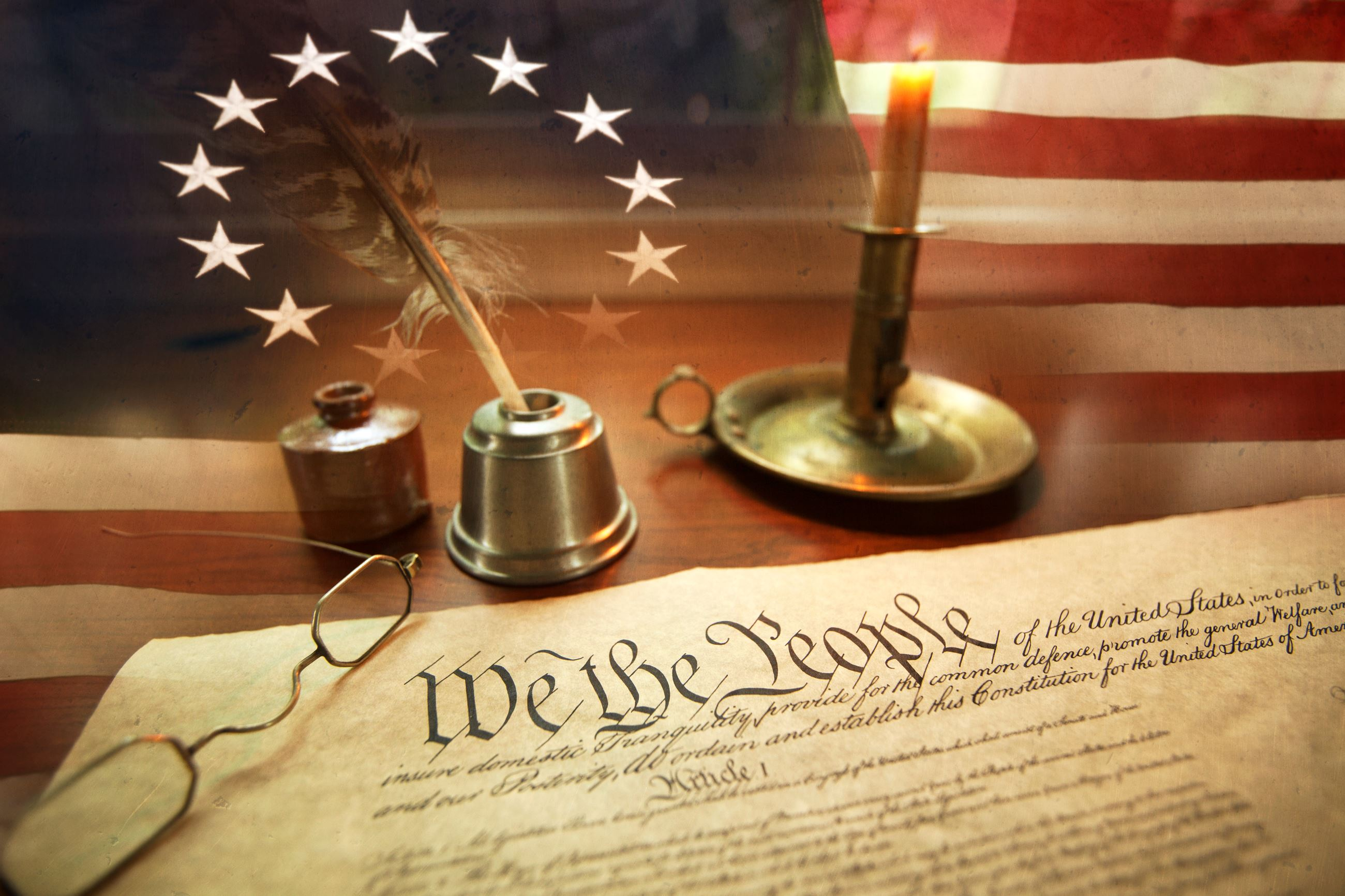 U.S. Constitution on early American flag with candle, quill, and spectacles.